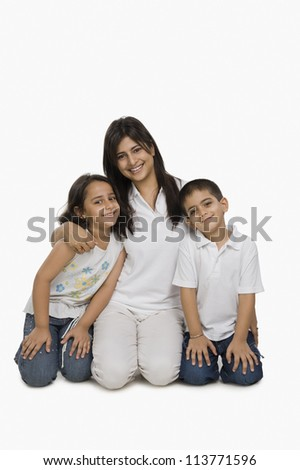 Mother hugging her children and smiling - stock photo