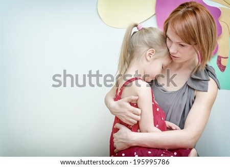 Mother hugging her sad child. - stock photo