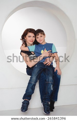 mother hugging her son, happy family, studio portrait - stock photo