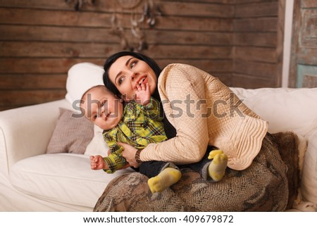 Mother hugging her son, the child poses a funny face. Cute little boy making grimaces, sincerity - stock photo