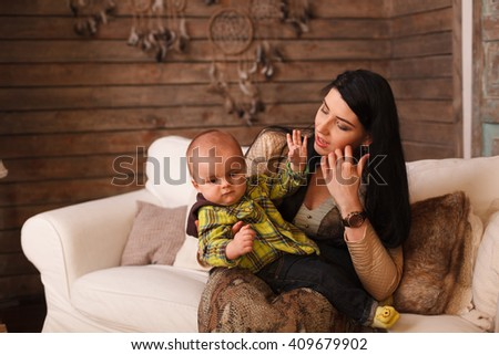 Mother hugging her son, the child poses a funny face. Cute little boy making grimaces, young mum, childhood, care - stock photo