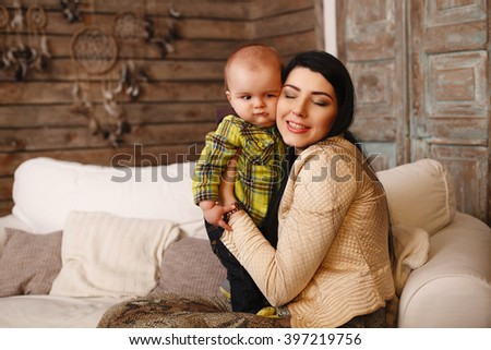 Mother hugging her son with closed eyes, the child poses a funny face. Cute little boy making grimaces - stock photo