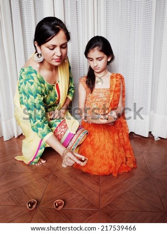 Mother illuminating diyas with her daughter on Deepawali festival in India. - stock photo