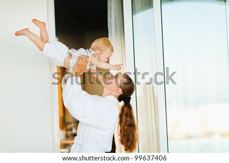 Mother in bathrobe playing with baby on terrace - stock photo