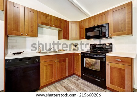 Mother in law kitchen room interior. Bright room with wooden cabinets and black appliances