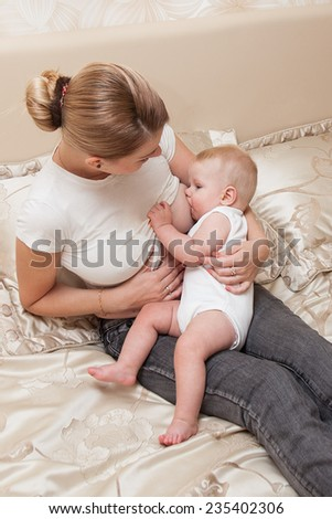 Mother in nursing bra and t-shirt nursing ( breastfeeding ) her baby, sitting on the bed at home - stock photo
