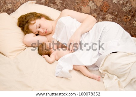 Mother is breast feeding a newborn baby lying down in bed. The symbol of happiness and motherhood - stock photo