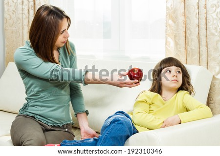 Mother is giving fruit to her daughter to eat but she is very angry,she don`t like fruit,I don`t want to eat fruit!