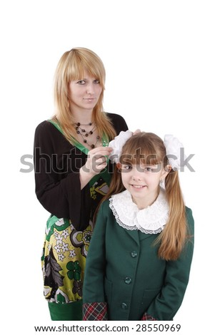 Mother is helping her's young daughter prepare to school. Woman is filleting ribbon on girl's hair.  Mom is brushing young schoolgirl's hair. Isolated on white in studio - stock photo