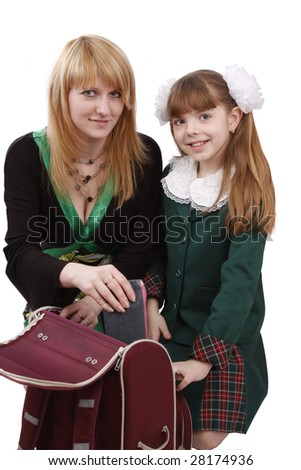 Mother is helping her's young daughter prepare to school. Woman is packing up schoolbag with schoolgirl.  Mom is helping to pack up girl's satchel. Isolated on white in studio. - stock photo