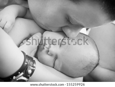 Mother is holding and kissing newborn - stock photo