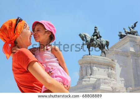 Mother is holding little daughter, equestrian monument to Victor Emmanuel II near Altar of fatherland in Rome, Italy - stock photo