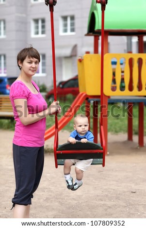 Mother is holding swing with her child - stock photo