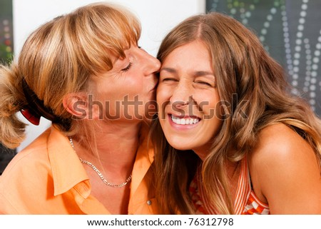 Mother is kissing her daughter as a sign of love