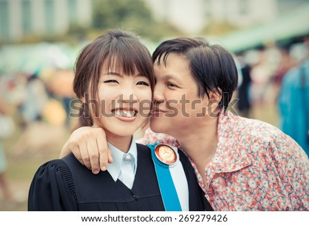 Mother is kissing her daughter with joy for her master degree graduation in Thailand university in vintage color - stock photo