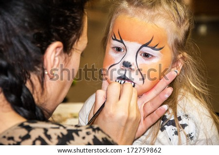 mother is preparing make-up for her daughter for a party - stock photo