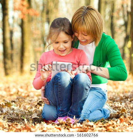 Mother is reading from tablet with her daughter, outdoor shoot - stock photo