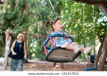 Mother is swinging her daughter in the park. - stock photo