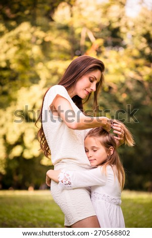 Mother is taking care of her daughter's hair - outdoor in nature - stock photo