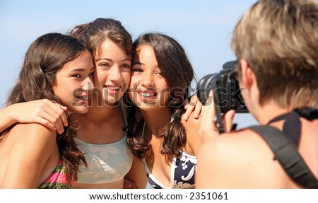 Mother is taking pictures of three teenage girls - stock photo