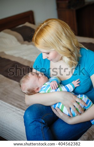 Mother keeps a little baby boy in her arms - stock photo