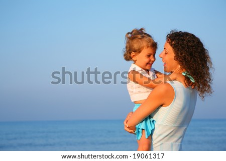 Mother keeps child at hands of edge of sea - stock photo