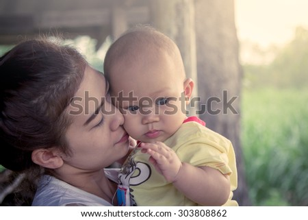 Mother kiss cute little boy with love in sweet soft color filter - stock photo