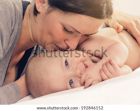 mother kissed her little baby, close-up with sun background - stock photo