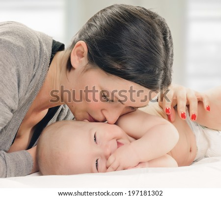mother kissed her little baby, close-up with window background - stock photo