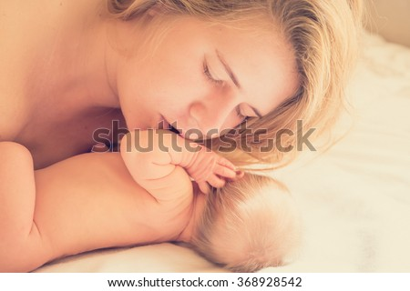 Mother kisses her newborn baby . The most tender moments of motherhood