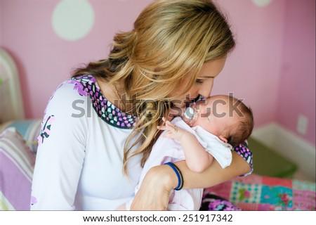 mother kisses her newborn daughter - stock photo
