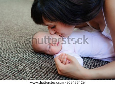 Mother kisses the little girl gently in a cheek which sleeps. Mother and daughter