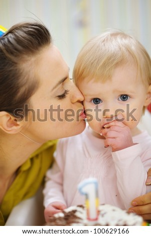 Mother kissing baby eating birthday cake - stock photo