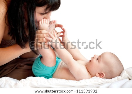 Mother kissing baby feet while play on a white bed - stock photo