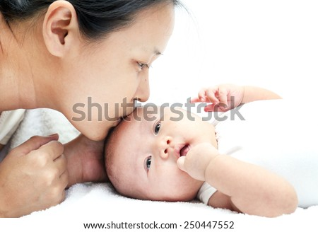 Mother kissing Baby . Happy Family (focus on woman)