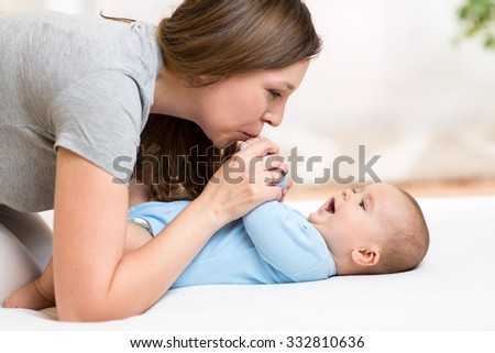 Mother kissing baby lying on bed in nursery - stock photo