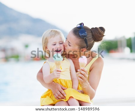 Mother kissing baby while eating ice cream - stock photo