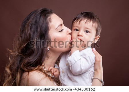 Mother kissing her baby child son on brown background in studio photo - stock photo