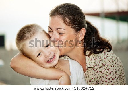 Mother kissing her child's cheek. - stock photo