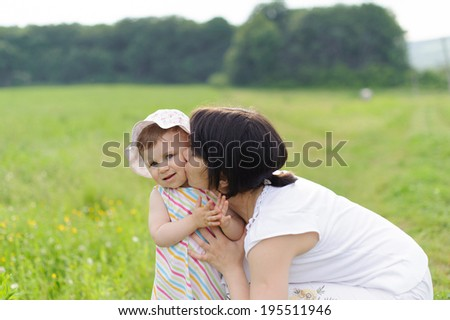 mother kissing her cute daughter in field - stock photo
