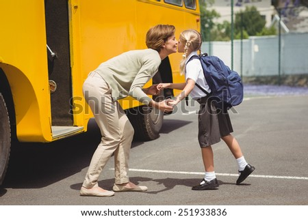 Mother kissing her daughter by school bus outside the elementary school - stock photo