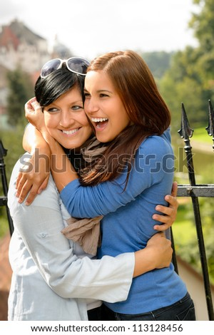 Mother kissing her daughter happy embrace outdoors teen leisure loving - stock photo
