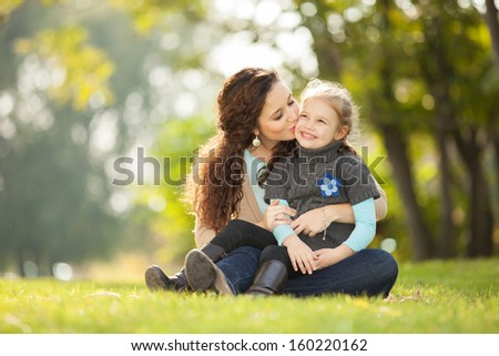 Mother kissing her daughter in the park - stock photo