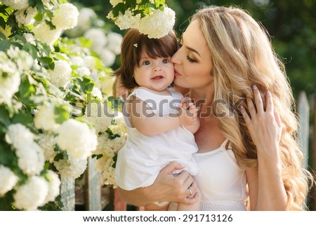 Mother kissing her daughter in the park. Woman kissing her baby girl. Woman with child outdoor in summer park. Happy family playing outdoor - stock photo