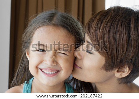 mother kissing her daughter' s cheek - stock photo