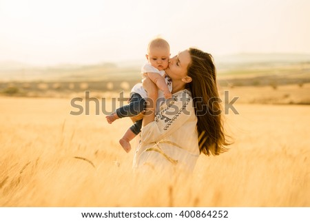 Mother kissing her daughter, summer landscape, wheat, hair flying in the wind - stock photo