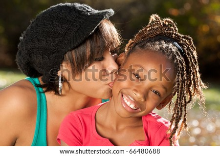 Mother Kissing her Happy Child - stock photo