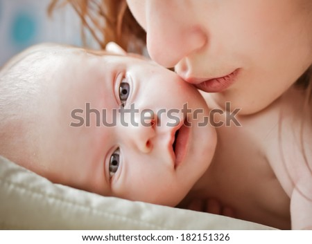 MOther kissing little baby . Baby laying on the pillow - stock photo