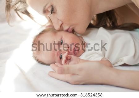 Mother kissing newborn baby - stock photo