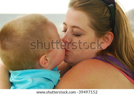 Mother kissing son , sallow depth of field, focus on mouth. - stock photo